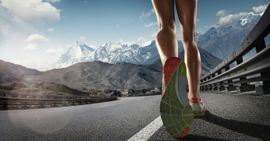 Sports background. Runner feet running on the road. Closeup on shoe